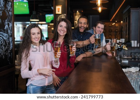 Perfect meeting with beer. Four friends are having fun in a pub and drinking beer - stock photo