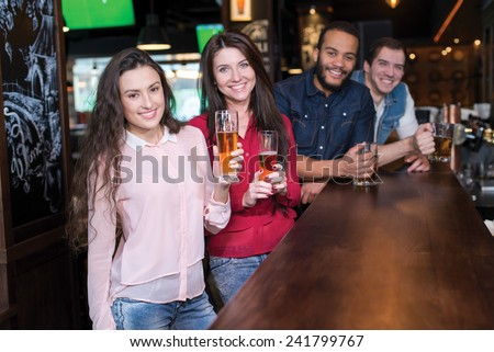 Perfect meeting with beer. Four friends are having fun in a pub and drinking beer. Friends and beer - stock photo