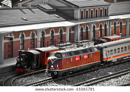 Perfect models of the older (steam) and newer (diesel) locomotives and passenger trains wait on the railway station. - stock photo