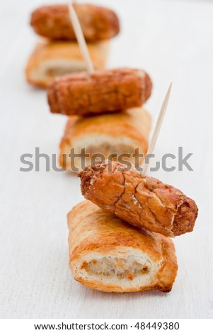 Perfect party snacks. A line of mini sausage rolls with cocktail sausages on a white plate - stock photo