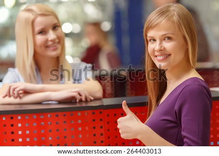 Perfect service. Selective focus on pretty young shopping woman showing thumbs up while standing by the information desk with smiling receptionist on the background - stock photo