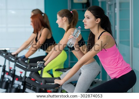 Perfect shape and ideal workout. Young and pretty woman is having training on exercise bike and drinks water. Her friends are also on exercise bikes are next to her. Active healthy workout in a gym. - stock photo