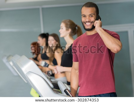 Perfect shape in a gym. Young and handsome African man is having training on a treadmill and makes a phone call. His friends are on treadmills on  background. Active workout. Healthy sportsmen concept - stock photo