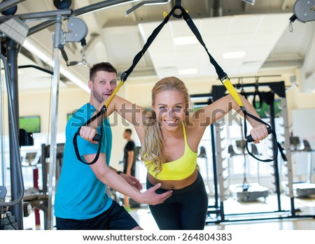 Perfect shape. Young and pretty girl is having training with her handsome athlete trainer. Active workout. Suspension training - stock photo