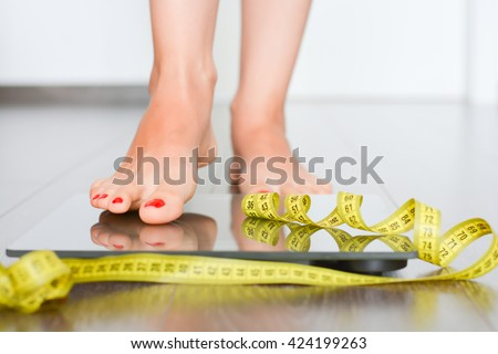 Perfect silhouette concept with woman on a weight scale - stock photo