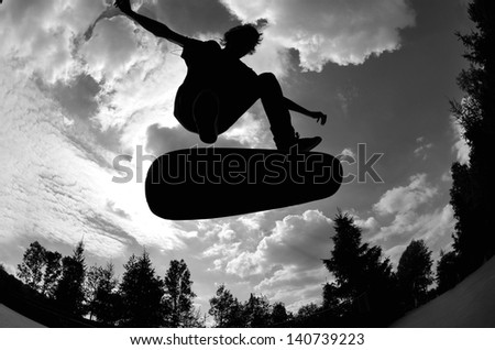 perfect silhouette of a skateboarder jumping high at the skate park. - stock photo