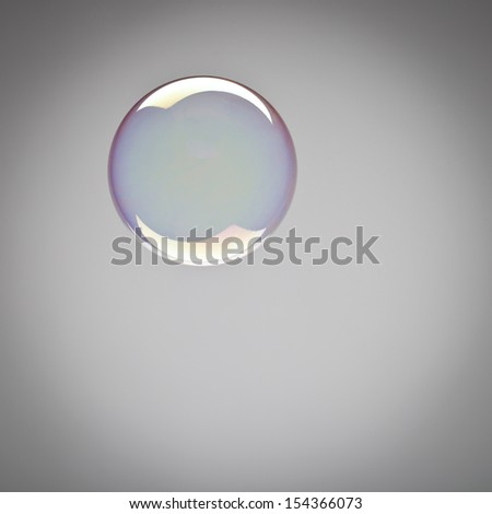 Perfect spherical shining soap bubble with iridescent reflections suspended mid air over a grey background with copyspace and vignetting - stock photo