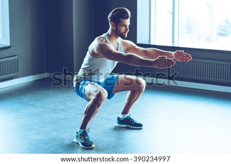 Perfect squat. Full length of young handsome man in sportswear doing squat at gym - stock photo