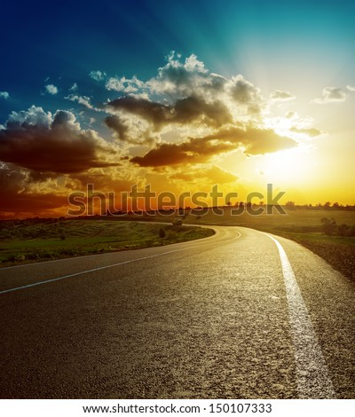 perfect sunset over asphalt road - stock photo