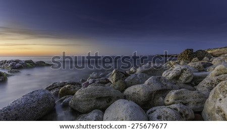 perfect sunset with big rocks in the ocean. amazing seascape - stock photo