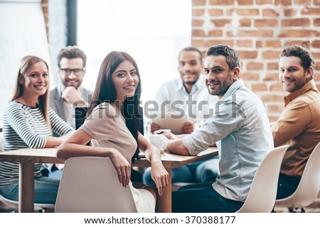 Perfect team. Group of six cheerful young people looking at camera with smile while sitting at the table in office  - stock photo