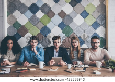 Perfect team. Group of young people looking at camera while sitting at the office table on business meeting  - stock photo