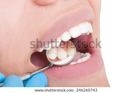 Perfect teeth and dentist mirror on white background - stock photo