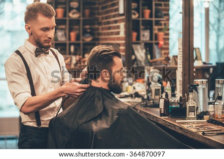 Perfect trim at barbershop. Young bearded man getting haircut by hairdresser with electric razor while sitting in chair at barbershop - stock photo