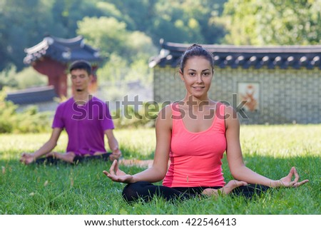 Perfect yoga. Beautiful young girl is balancing doing yoga. Pair yoga concept. Yoga outdoor class workout Acro-yoga. - stock photo