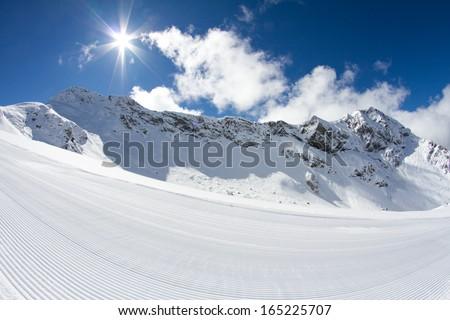perfectly groomed empty ski piste - stock photo
