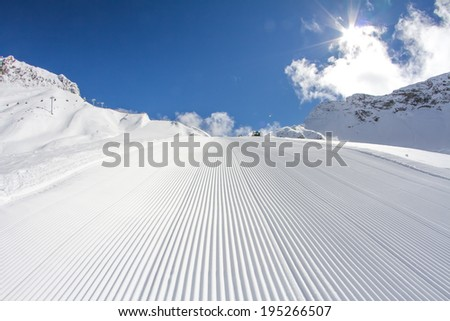 perfectly groomed empty ski piste - stock photo