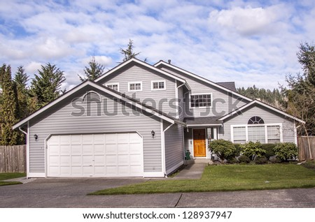 perfectly manicured old suburban house on a beautiful sunny day - stock photo