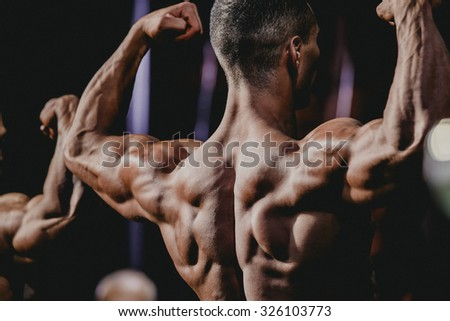 performance athlete bodybuilder to competition. demonstration of biceps your arms from behind closeup - stock photo