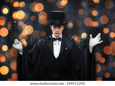 performance, circus, show concept - magician in top hat and cape showing trick with magic wand over nigh lights background - stock photo