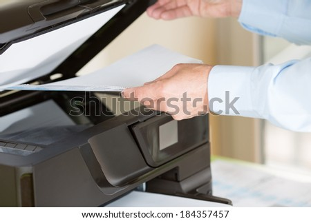 Performing a photocopy clerk with multifunction printer - stock photo