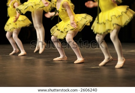 Performing on stage, a group of young dancers show off their talent and bright costumes - image highlights a narrow depth of field - stock photo