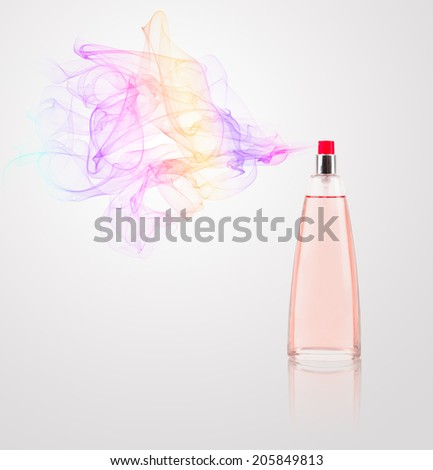 Perfume bottle spraying colorful scent - stock photo