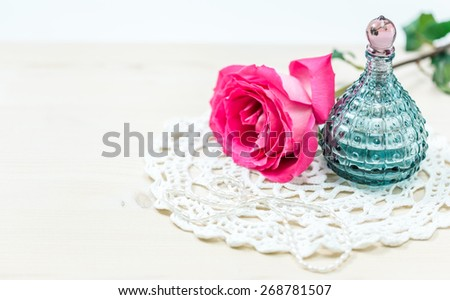 Perfume bottle with pink rose on table close-up - stock photo