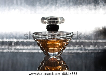 Perfume bottle with reflection on silver - stock photo
