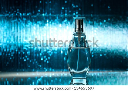 Perfume on abstract blue shiny background - stock photo