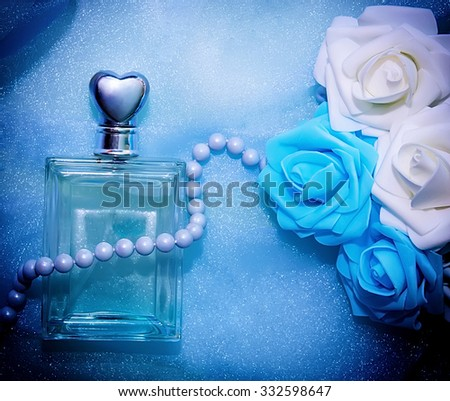 Perfume, pearls and flowers on a blue background. Women's accessories. - stock photo