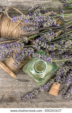 Perfumed herbal oil essence and lavender flowers. Vintage decoration. Top view. Selective focus - stock photo