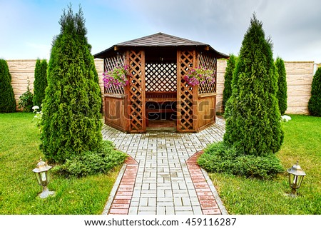 Pergola in the garden, pavilion in an urban garden for recreation, wooden lounge outdoors, peaceful gazebo set in a mature garden, blue sky sunny and cloudy - stock photo