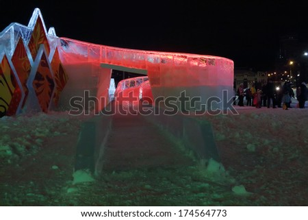 PERM, RUSSIA - JAN 11, 2014: Illuminated red ice slide in Ice town at evening. Construction of Ice town of Perm was spent 590 thousand dollars. - stock photo