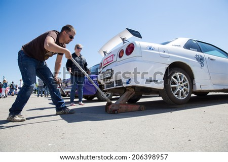 "Perm, Russia - June 7,2014. Avto - moto festival ""Resox Tuning Fest 3"".man jacking  car behind - stock photo"