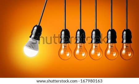 Perpetual motion with LED bulb and simple light bulbs - stock photo