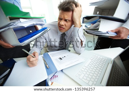 Perplexed accountant looking at huge piles of documents held by his business partners while doing financial reports - stock photo