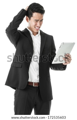 Perplexed businessman using a tablet - stock photo