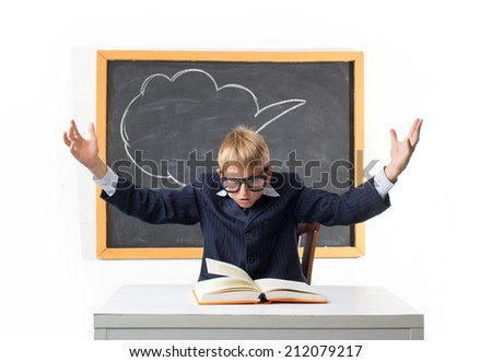 Perplexed schoolboy looking in textbook - stock photo