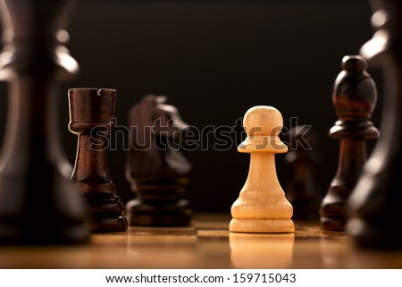 Perseverance in the face of a challenge, a conceptual image of a lonely light coloured wooden pawn standing on a chessboard surrounded by all the black chess pieces, low angle view - stock photo