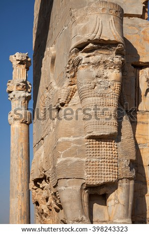 Persian Lamassu and a column with typical Achaemenid architecture in the ruins of ancient city of Persepolis in Shiraz. - stock photo