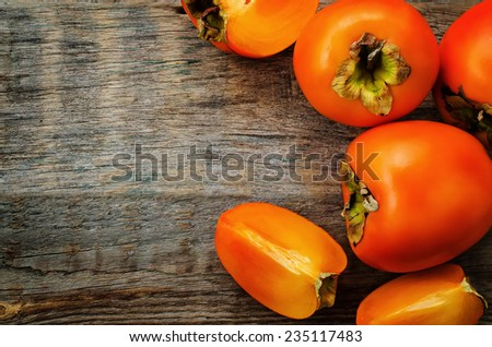 persimmon on a dark wood background. tinting. selective focus - stock photo