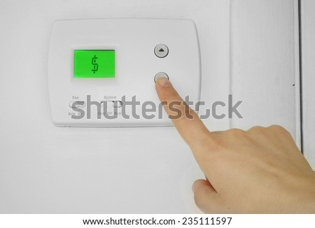 Person adjusting a wall thermostat with dollar sign symbol on the display                                - stock photo