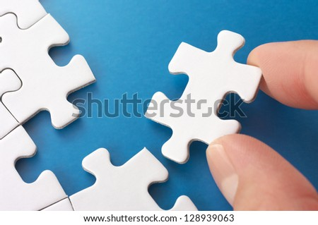 Person assembling puzzle pieces.Concept image of building and growth. - stock photo