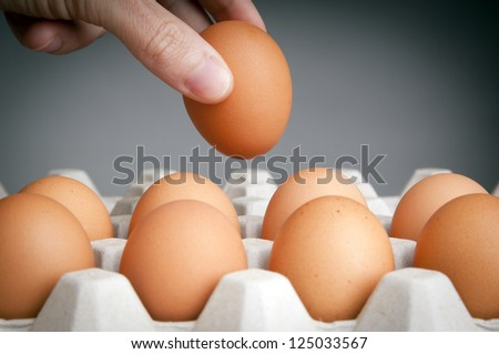 Person choosing the best egg from a carton of eggs - stock photo