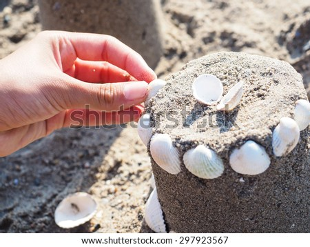 Person creating a sand castle with white clams - stock photo