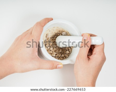 Person crushing brown sugar in a white marble mortar - stock photo