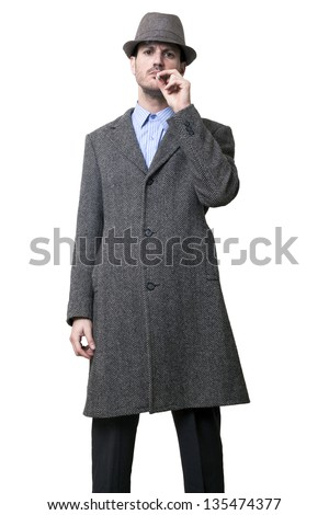 Person dressed in a gray overcoat and hat. His left hand holding a cigarette to his lips, taking a puff while staring to the camera with a serious expression on his face. Isolated on white background. - stock photo