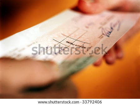 Person handing over check in financial transaction. - stock photo