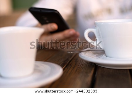 Person holding a mobile phone while drinking coffee with milk outdoors - stock photo